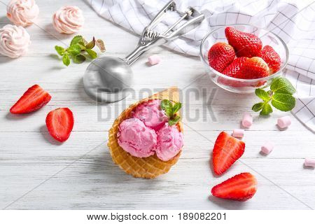 Wafer cone with strawberry ice-cream on wooden table