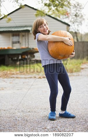 Caucasian girl holding pumpkin at pumpkin patch