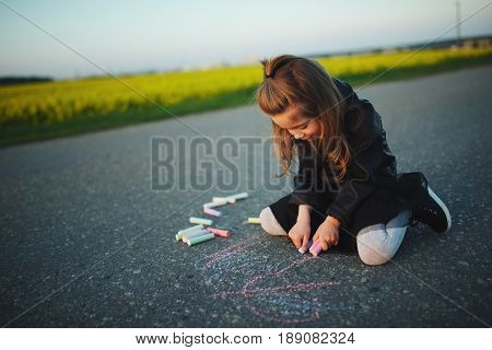 little happy girl draws pictures on asphalt