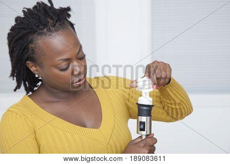 Black woman using CFL light bulb