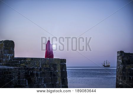 Caucasian woman with lantern overlooking ocean