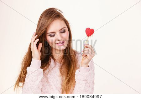 Romantic gestures valentines gifts ideas concept. Happy flirty woman holding red wooden heart on stick.