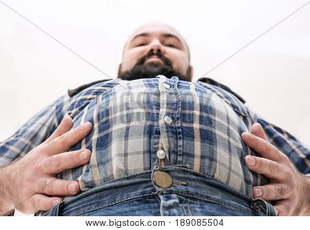 Adult man in small shirt and jeans on light background. Weight loss concept