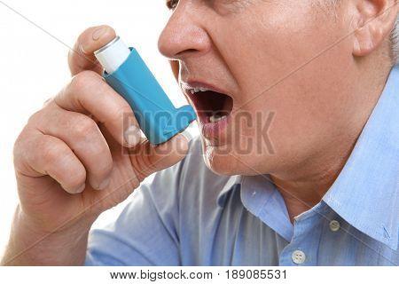 Elderly man using inhaler, closeup