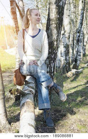 young woman sits on a trunk of the tumbled down birch