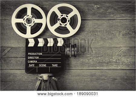 Old movie camera consisting of a tripod lens film reels and clapperboards.Toned photo.