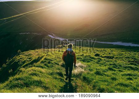 Young man in red jacket walking on a path towards Durdle Door alongside Jurassic Coast, Dorset, England during sunset. Green grass and hill soaked in the sun.