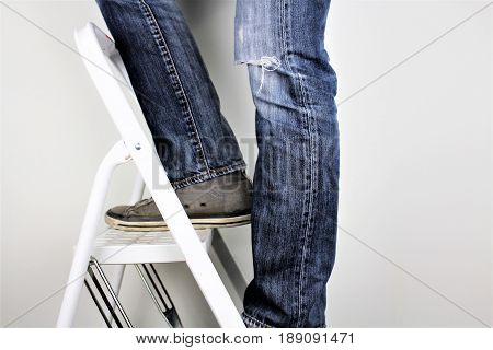 Anonymous man reaching on top of ladder climbing, indoors studio people shot.
