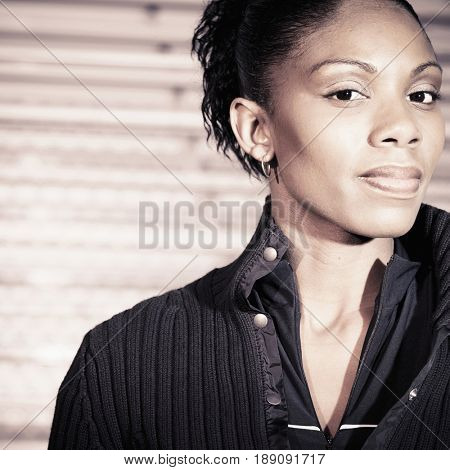 African American woman standing by bleachers