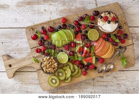 Fruit and yogurt for breakfast on a wooden cutting board.