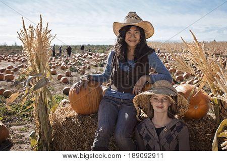 Girls wearing straw hats in pumpkin patch