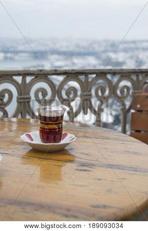 Soğuk kış gününde masada duran sıcak çay bardağı