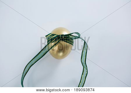 Close-up of golden Easter egg tied with ribbon on white background