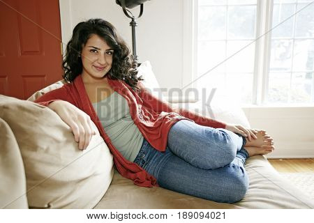 Middle Eastern woman relaxing on sofa