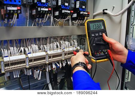 engineer tests the industrial electrical circuits with a multimeter in the control terminal box. Engineer's hands with a multimeter close-up against background of terminal rows of automation panel.