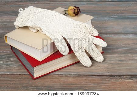 Open book, hardback books on wooden table, rose and white gloves knitted crochet Back to school. Copy space for text