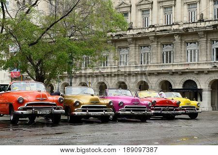 HAVANA CUBA - 10 DECEMBER 2016: Old American colourful cars serving as taxis for tourists in order to go on a tour of old Havana standing in the Central Park in the heart of Havana
