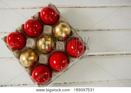 Red and golden Easter eggs in the carton on wooden background