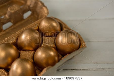 Close-up of golden Easter eggs in the carton on wooden background