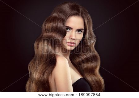 Healthy Hair. Brunette Girl Portrait With Long Shiny Wavy Hair. Beautiful Model With Curly Hairstyle
