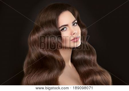 Healthy Hair. Beautiful Model Girl With Shiny Brown Wavy Long Hairstyle And Makeup Isolated On Black