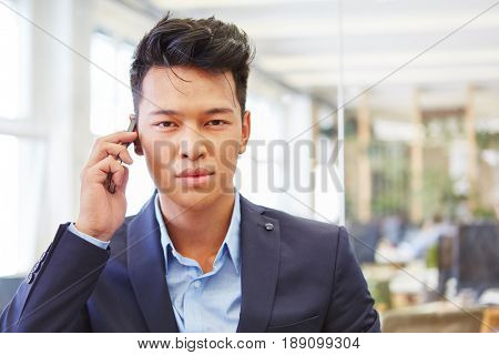 Young asian man as consultant on the phone using smartphone