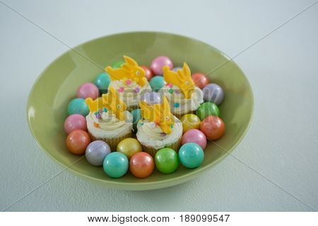 Close-up of colorful chocolate Easter eggs with cup cakes in bowl