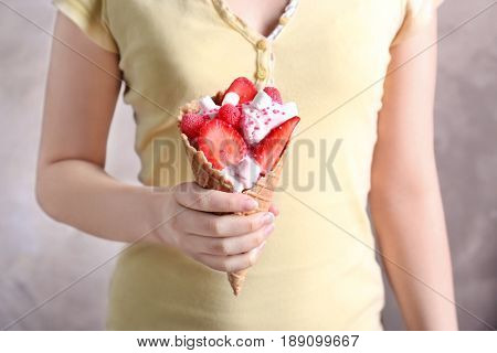 Woman holding ice-cream cone on light background