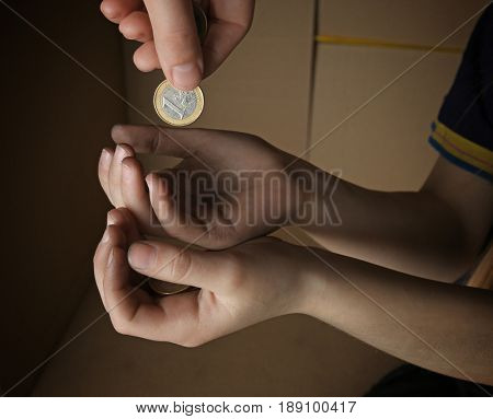 Female hand putting coin into hands of poor child, closeup