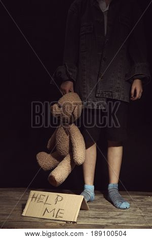 Poor little girl with toy bear and piece of cardboard on black background