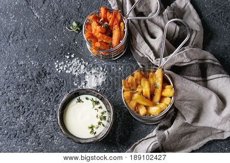 Variety of french fries traditional potatoes, sweet potato, carrot served with white cheese sauce, salt, thyme in frying basket over dark texture background. Top view with space. Homemade fast food