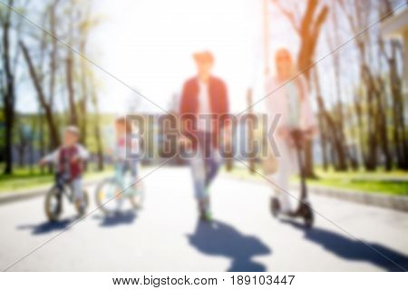 Blurred image of family on bicycle during day