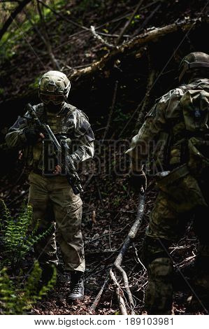 Military officer with weapons on reconnaissance in forest among trees