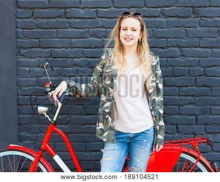 Camo Utility Overcoat. A beautiful girl in a fashionable outfit posing with a trendy vintage red bicycle on the street. Outdoor.