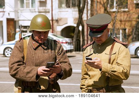Khabarovsk Russia - May 9 2017: Two men wearing vintage military uniform texting on smartphones. Funny incongruous USSR soldiers holding cellphones