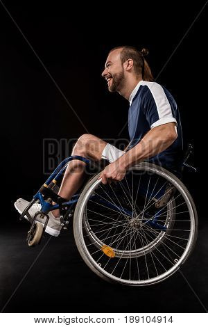Happy Paralympic In Wheelchair Dressed In Sportswear Isolated On Black