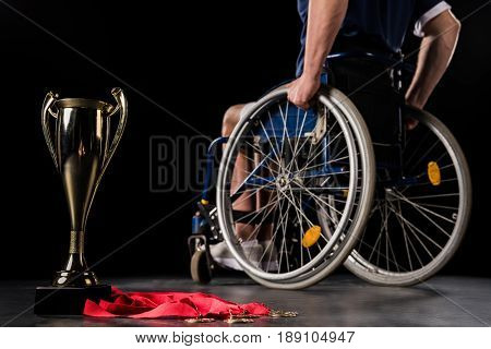 cropped view of paralympic in wheelchair going away from his champion goblet and gold medals isolated on black