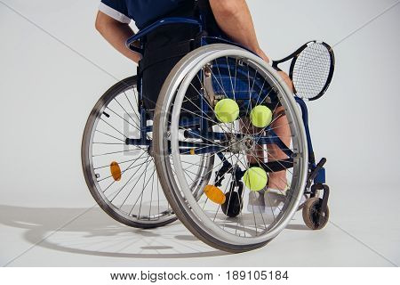 Cropped View Of Tennis Player Sitting In Wheelchair With Tennis Racquet And Balls Isolated On Grey