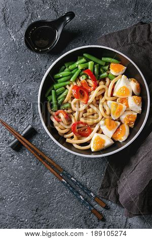 Cooking stir fry udon noodles, green beans, sliced paprika, boiled eggs, soy sauce with sesame seeds in black plate with wood chopsticks over black texture background. Flat lay. Asian style dinner