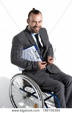 Smiling Physically Handicapped Businessman In Wheelchair Holding Clipboard With Contract