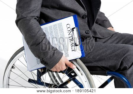 Physically Handicapped Businessman In Wheelchair Holding Clipboard With Contract
