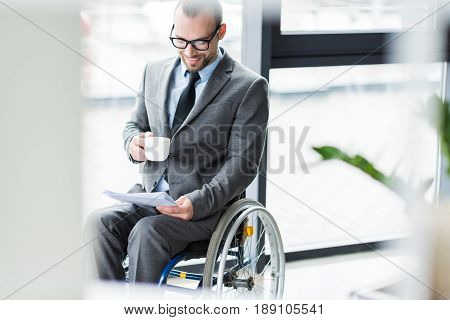 Smiling Physically Handicapped Businessman Drinking Coffee And Looking At Documents