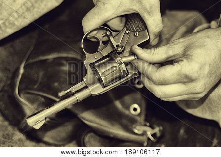 The soldier loads the cartridges in the gun close-up. Weapons retro style