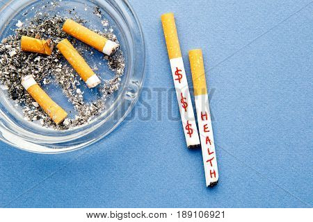 Stop Smoking - Health and Money - with cigarettes and ashtray on blue background