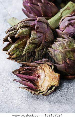 Uncooked whole and sliced organic wet purple artichokes over gray texture background. Close up