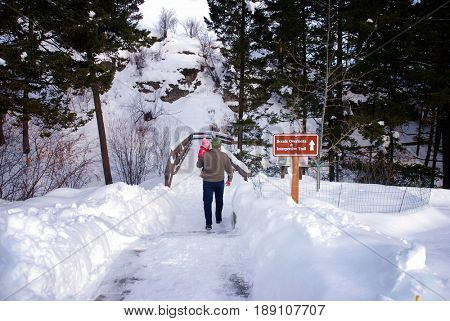 Father carries his baby daughter on a snow-covered interpretive trail at Lone Pine State Park, Kalispell, Montana
