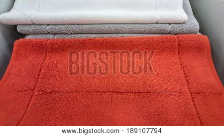 Fluffy Bathing Towels In Red, Gray And White Colors Stacked On Shelf For Sale In A Store