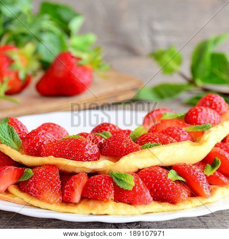 Fresh strawberry egg omelet. Omelet filled with strawberries slices and garnished with mint leaves on a plate. Fresh strawberries and mint leaves on vintage table. Sweet omelet with berries recipe
