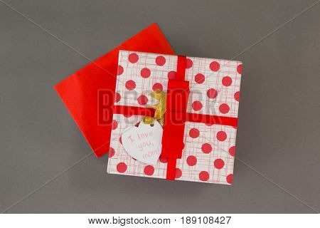 Gift box with I love you mom tag on grey background