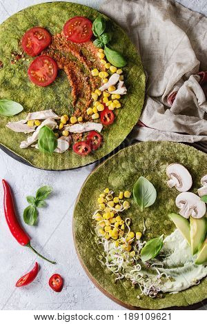 Green spinach matcha tortillas with ingredients for filling ready to wrap. Corn, avocado, green paprika, sprouts, mushrooms, chicken, meat served over gray texture background and textile. Flat lay